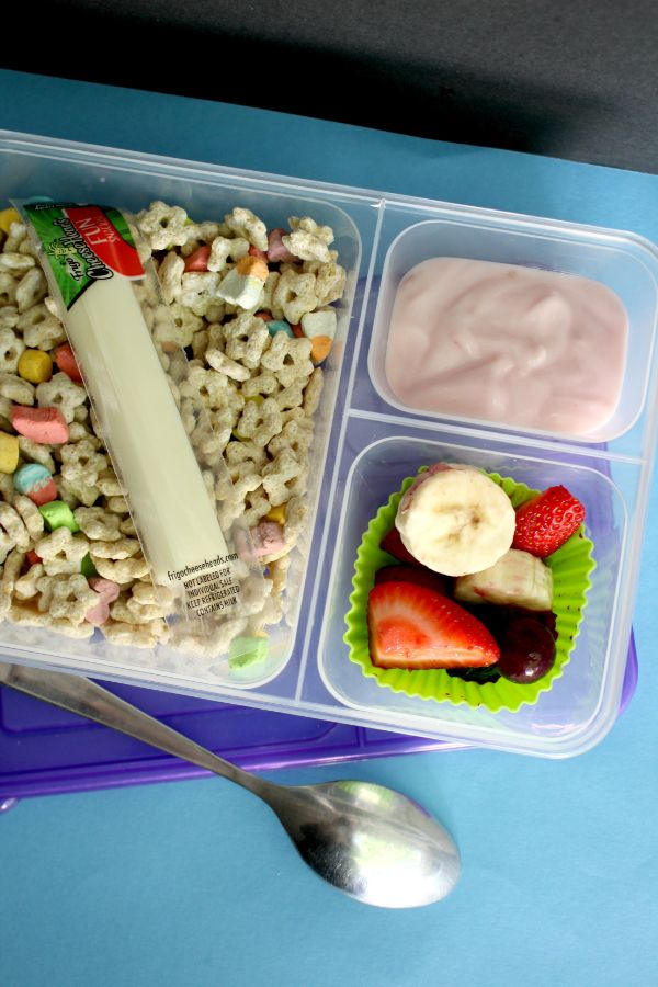 cereal lunch box with a cheese sick, yogurt and fruit
