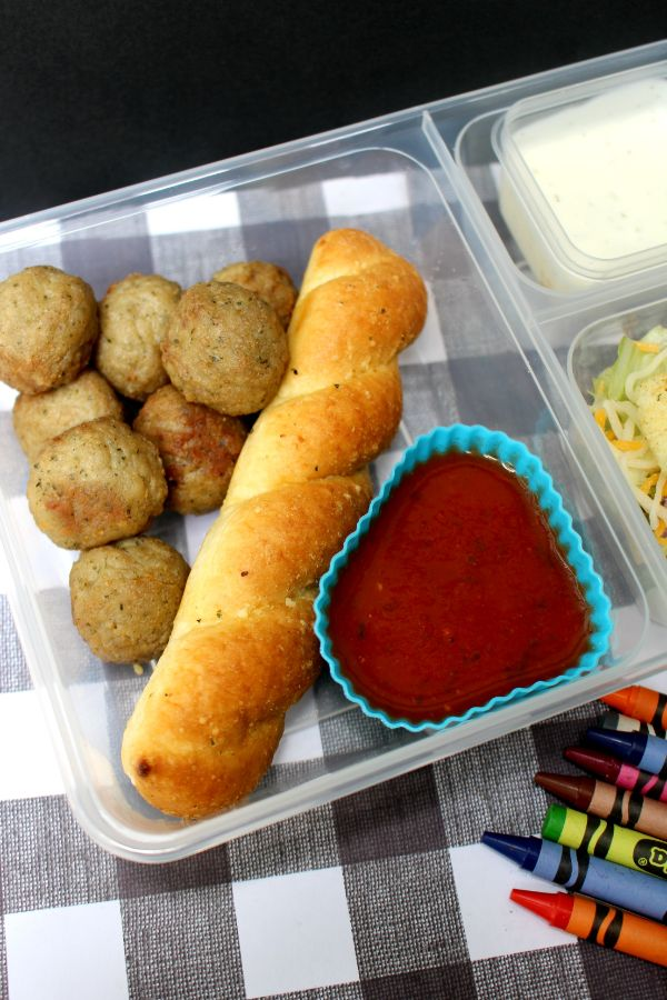 meatball lunch box with a breadstick and sauce