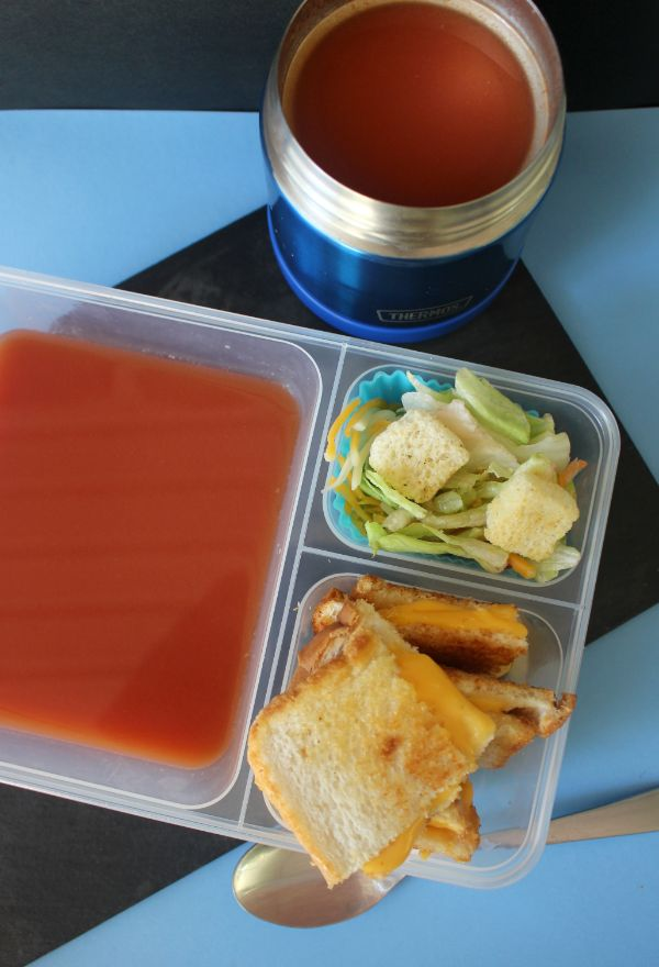 grilled cheese lunch box with a salad and tomato soup