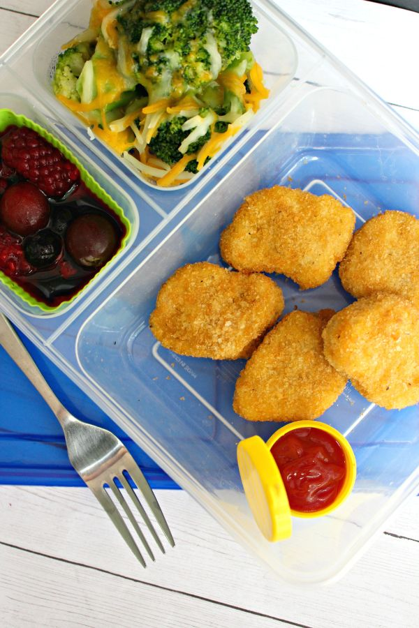 nuggets lunch box with ketchup, broccoli and fruit