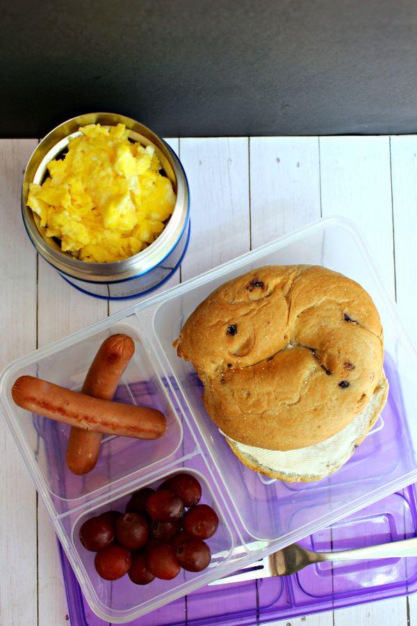 a plastic container with bagel, hot dogs, grapes next to a mug of scrambled eggs as Cold lunch ideas for kids