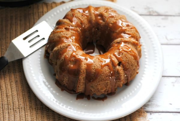 Instant Pot Caramel Apple Bundt Cake on a white plate next to a metal spatula on a brown mat
