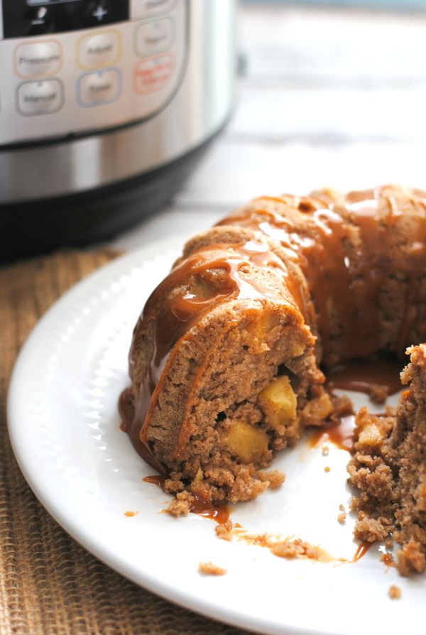 Instant Pot Caramel Apple Bundt Cake with a piece cut out of it on a white plate on a brown mat with an instant pot in the background