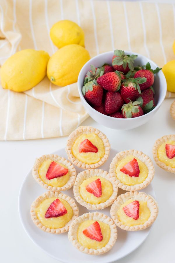 mini strawberry lemon tarts on a white plate next to lemons and strawberries in a white bowl