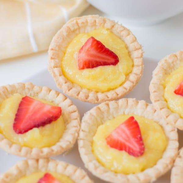 a close up of mini strawberry lemon tarts on a white plate