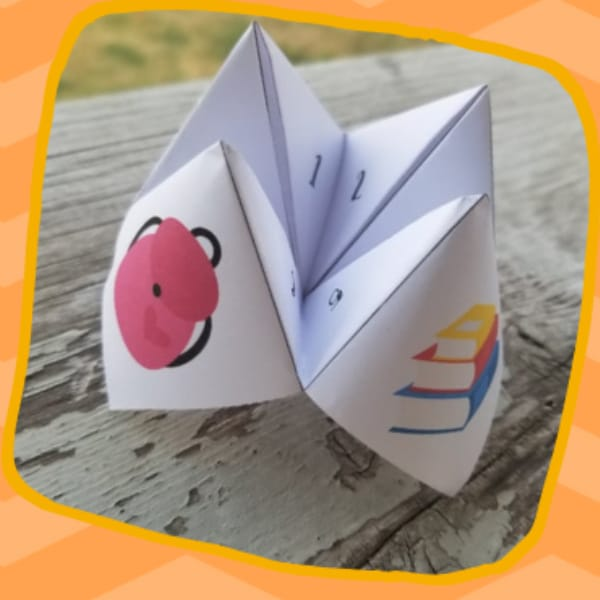 printable back to school chatterbox game on a wood table surrounded by an orange frame graphic