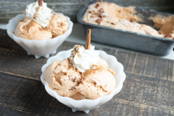 homemade pumpkin pecan ice cream in two white bowls and in a freezer pan