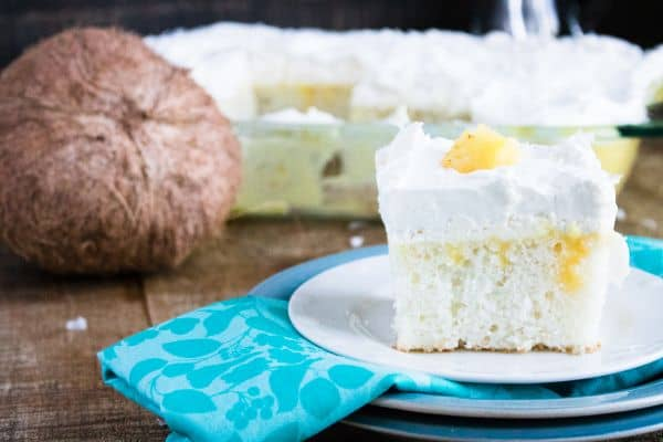 close up of pina colada poke cake on plate with a coconut and more cake in a glass dish in the background