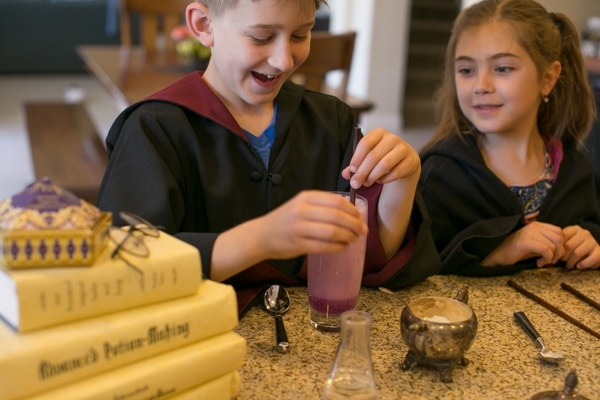 a boy and a girl working on an activity on a kitchen counter next to a stack of books