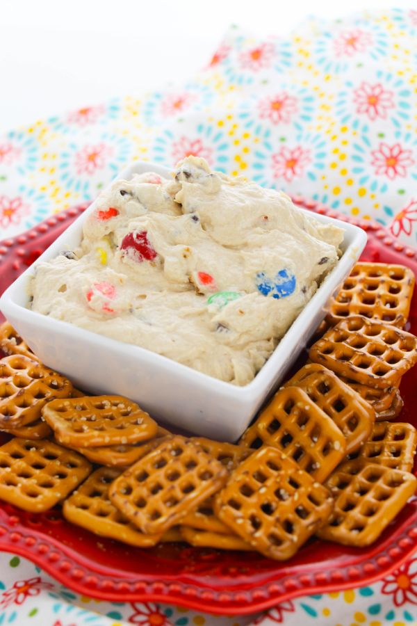 Cream Cheese Monster Cookie Dough Dip in a white dish next to pretzels on a red plate on a multi-colored cloth