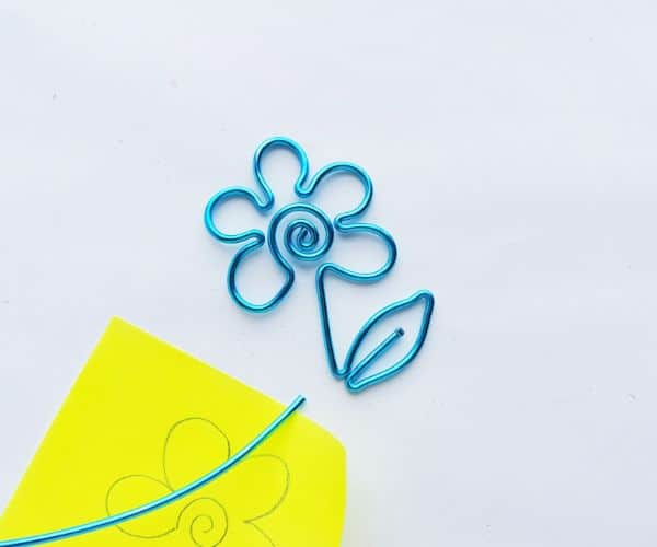 how to make a wire bookmark by cutting the wire left under a leaf, and a yellow printable flower template on a white background