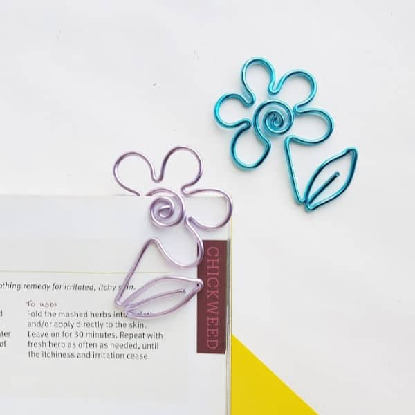 2 DIY wire flower bookmarks on a white background and clipped to some papers