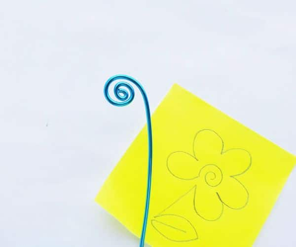 how to make a wire bookmark by first swirling an end, and a yellow printable flower template on a white background