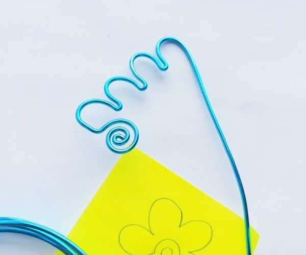 how to make a wire bookmark by making a scalloped line, and a yellow printable flower template on a white background