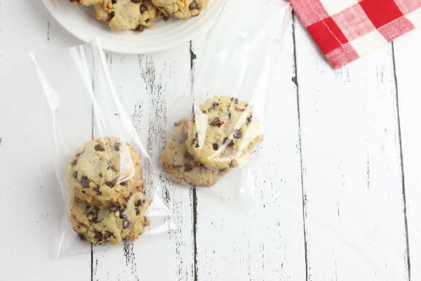 cookies in 2 cellophane bags next to a partial view of cookies on a white plate