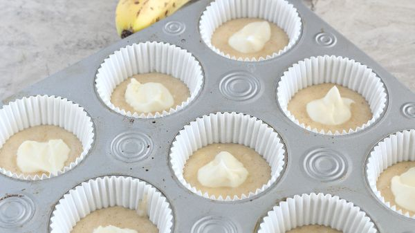 batter for Cream Cheese Filled Banana Bread Muffins in a muffin tin topped with some cream cheese