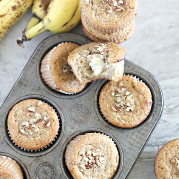 Cream Cheese Filled Banana Bread Muffins in a muffin tin and on a table next to bananas