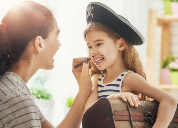 a lady using a black makeup pencil to draw a mustache on a girl dressed as a pirate