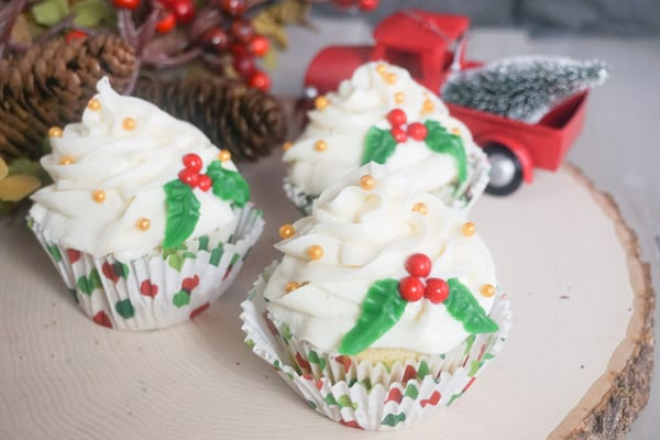 three Christmas holly cupcakes on a log with pincecones and a red truck in the background