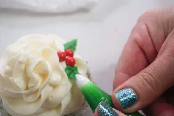 a hand adding green frosting that looks like leaves to a frosted cupcake
