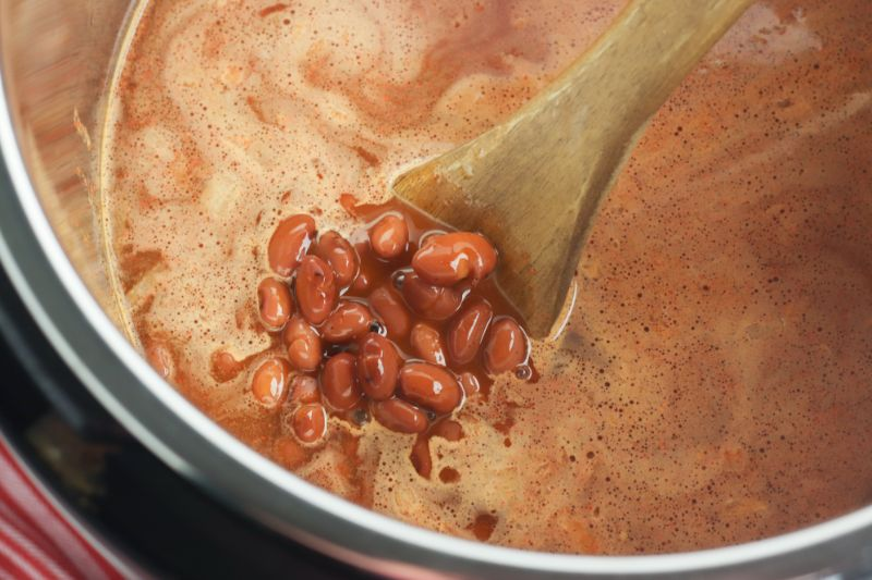 Chili beans in an instant pot with a brown spoon.