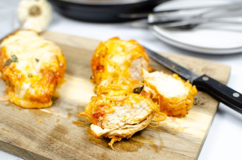 Chicken parmesan chopped into pieces on a wooden chopping board next to a knife.