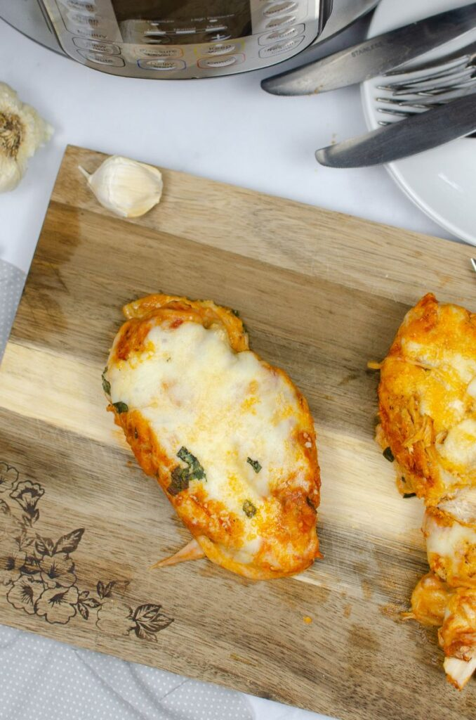 Cheese topped chicken parmesan on a wooden chopping board next to an instant pot.