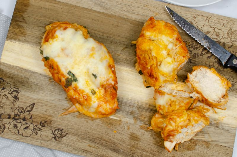 Whole chicken parmesan breast and chopped chicken parmesan on a wooden chopping board.