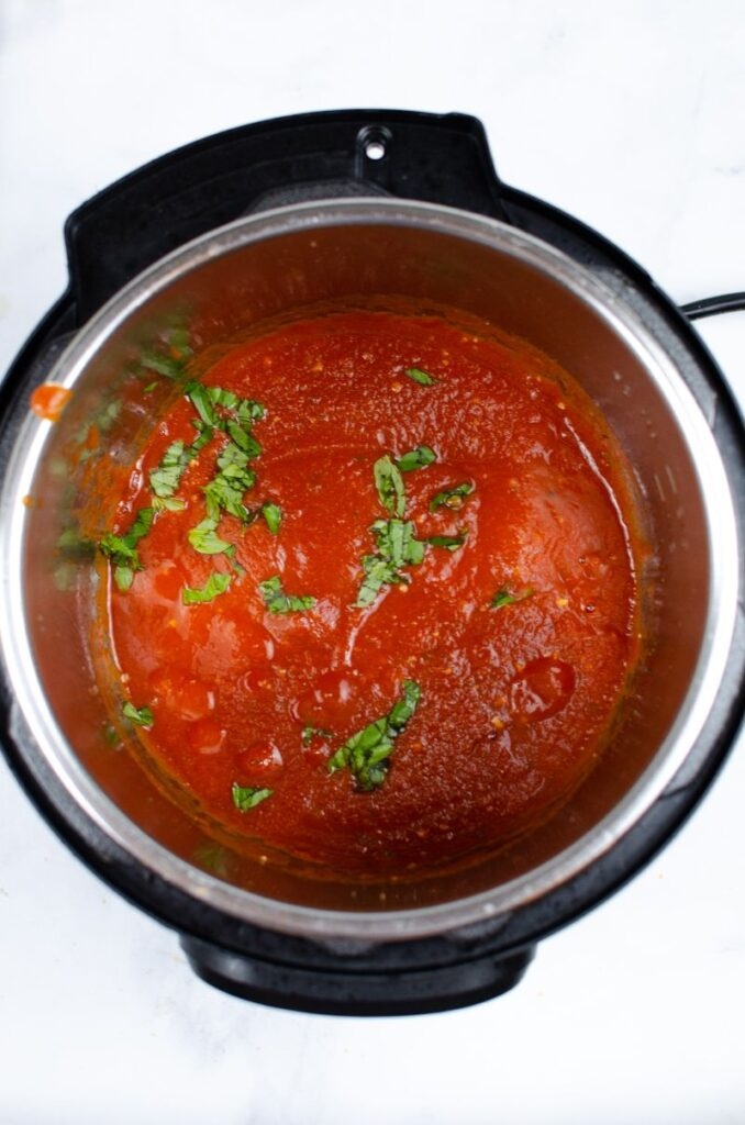 Sauce mixture in an an instant pot topped with fresh basil.