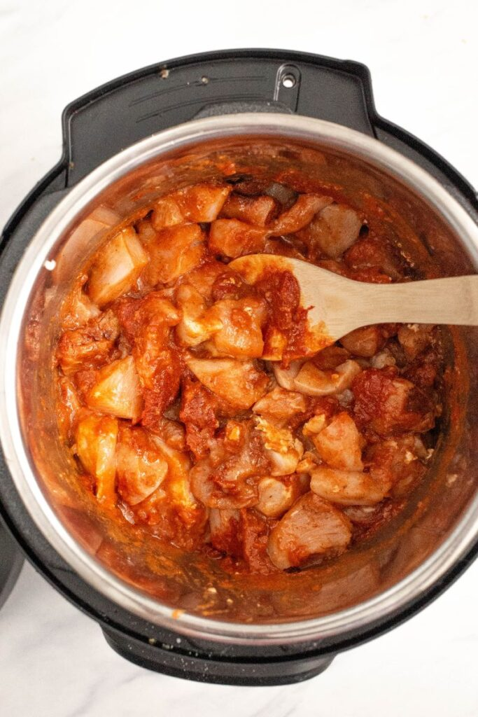 Chicken pieces mixed with spices in an instant pot.
