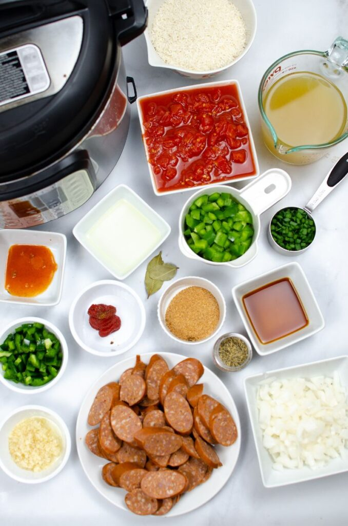 Sausages, veggies, and other ingredients for the jambalaya recipe in bowls on a table.