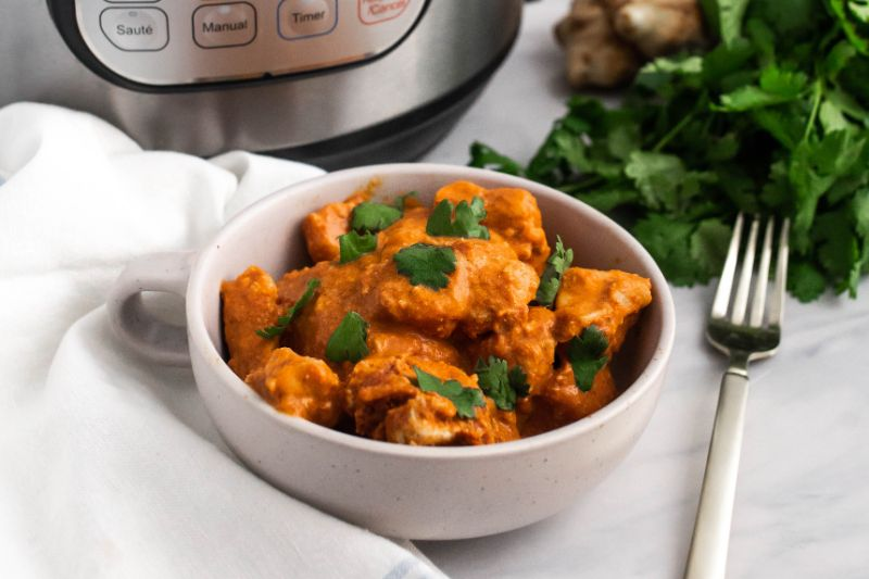 Chicken tikka masala in a white bowl next to a fork, cilantro, ginger and an instant pot.