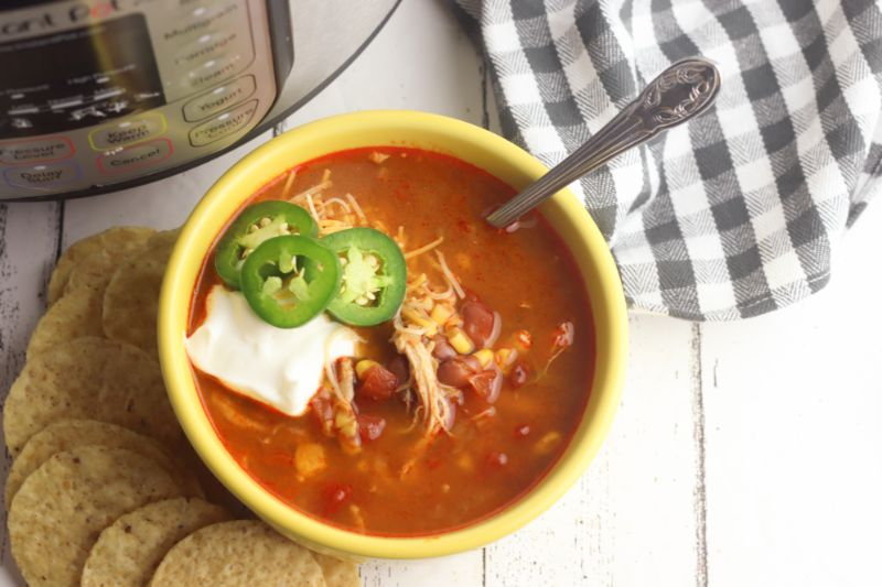 Mexican tortilla soup topped with sour cream and jalapenos in a yellow bowl next to tortilla chips and an instant pot.