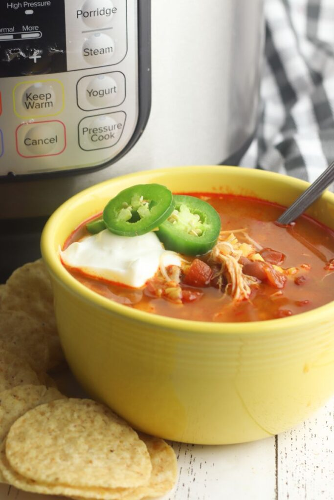 Mexican tortilla soup topped with sour cream and jalapenos in a yellow bowl in front of an instant pot.