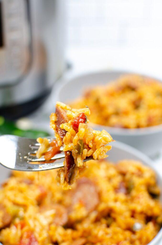 Jambalaya rice and sausage on a fork above two white bowls of jambalaya.