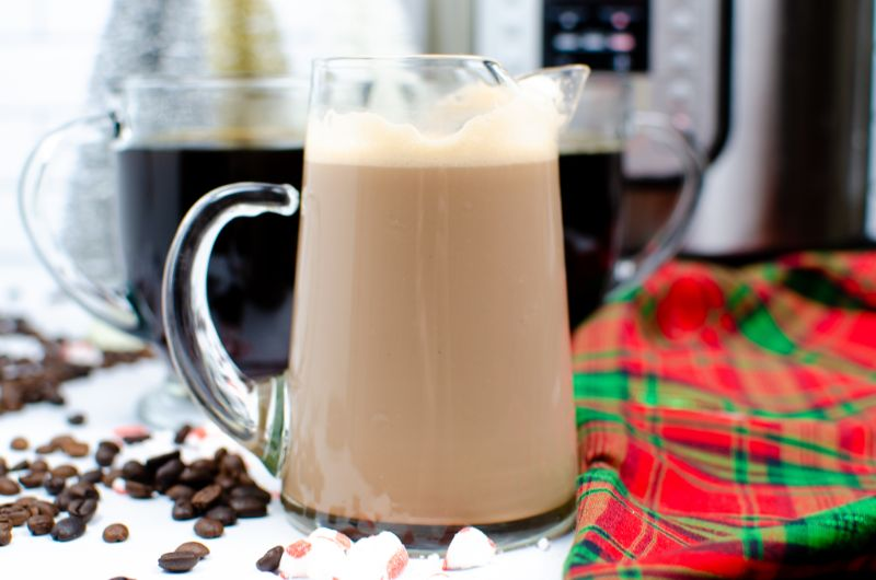 Instant Pot Peppermint Mocha Creamer and coffee in a glass mug next to peppermints, coffee beans, and a green and red cloth  with coffee in glass mugs and an instant pot in the background