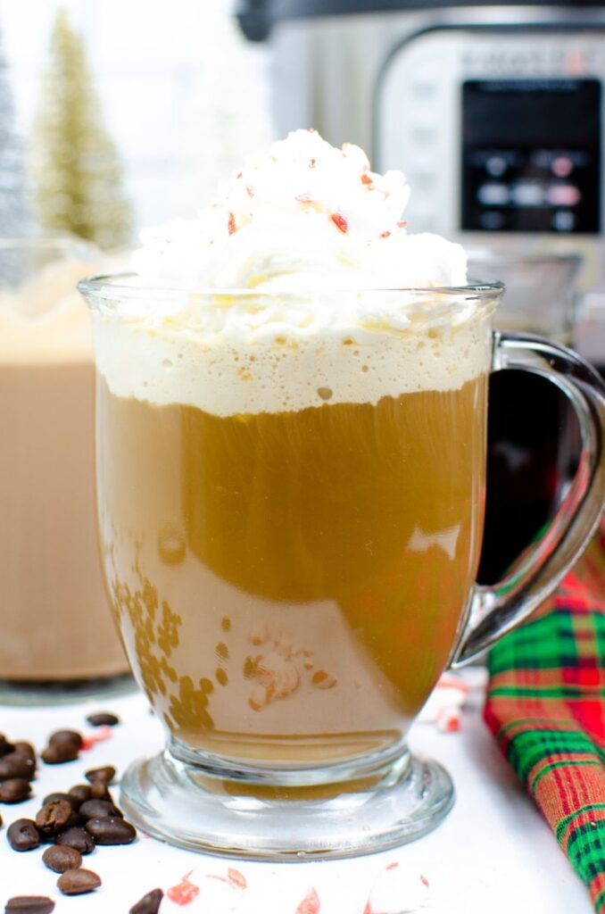 Instant Pot Peppermint Mocha Creamer and coffee in a glass mug topped with whipped cream next to peppermints, coffee beans, and a green and red cloth  with coffee in glass mugs and an instant pot in the background