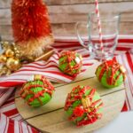 christmas hot cocoa bombs on wooden platter with tree in background