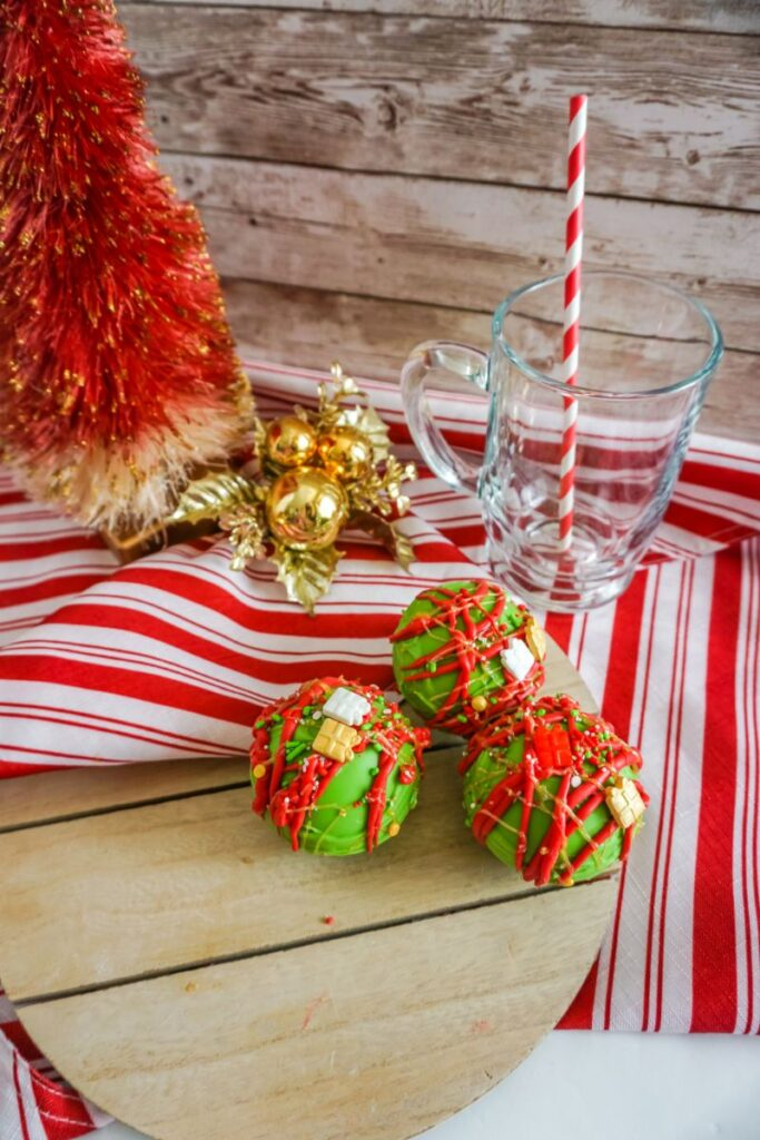 Christmas Hot Cocoa Bombs on wooden serving tray next to a red and white striped cloth and a glass mug with a straw in it