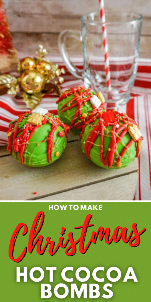 Christmas Hot Cocoa Bombs on wooden serving tray next to a red and white striped cloth and a glass mug with a straw in it with title text reading How to Make Christmas Hot Cocoa Bombs