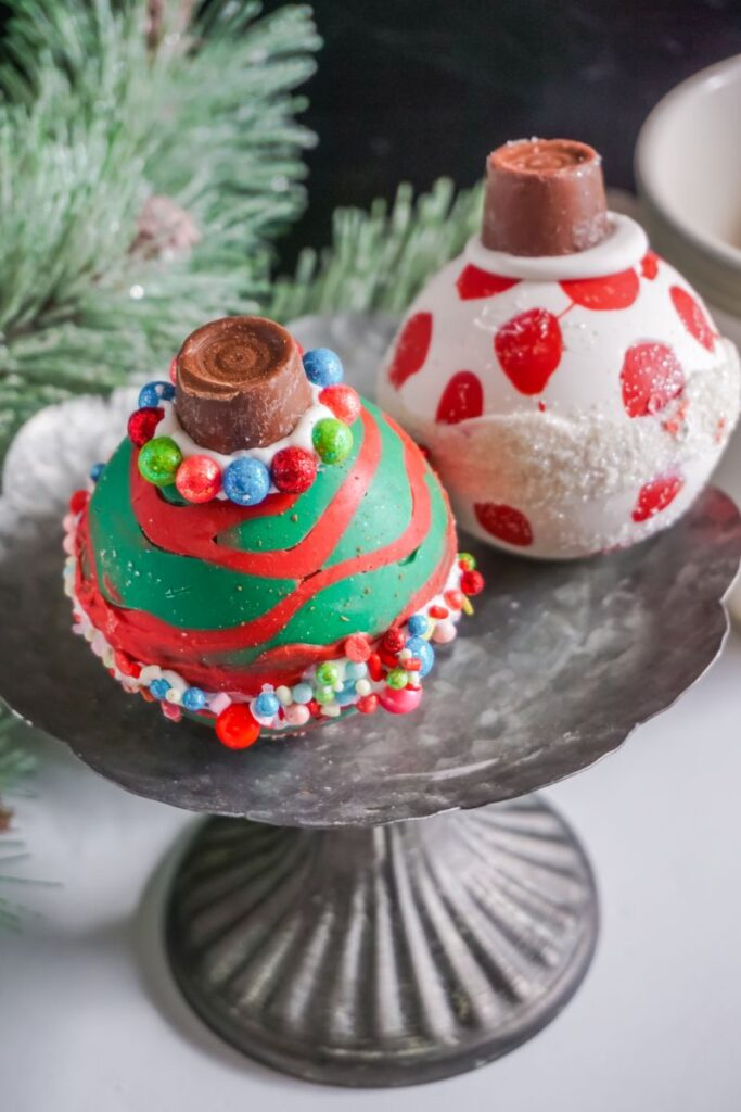 Christmas Ornament Hot Cocoa Bombs  on metal stand with part of a Christmas tree in the background