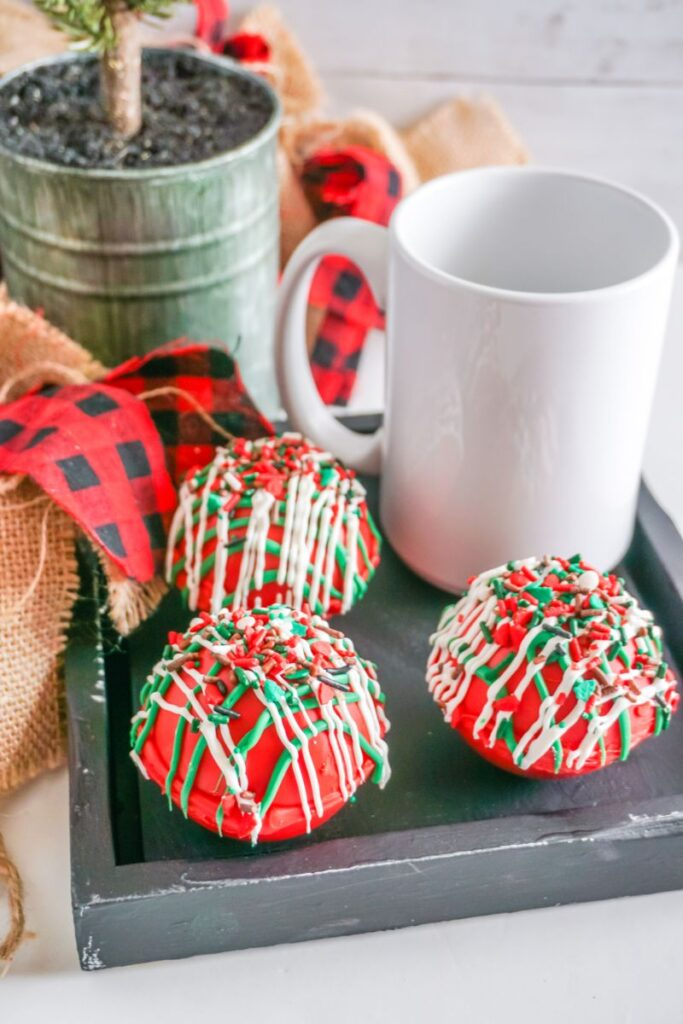 three Christmas Taffy Hot Cocoa Bombs next to a white mug on a wooden serving tray with a plant, red and black checked cloth, and burlap cloth in the background