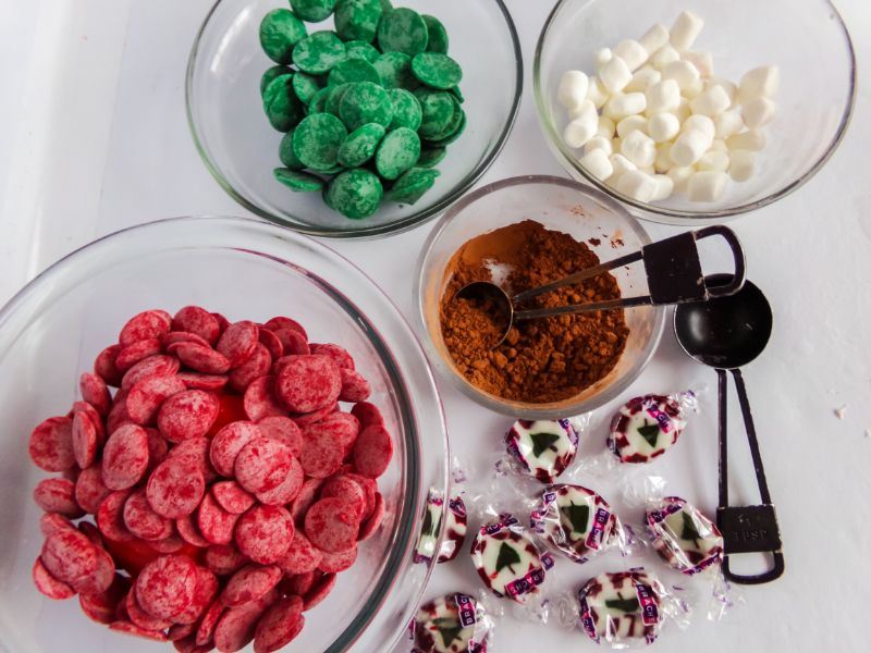red and green candy melts, mini marshmallows and hot chocolate mix in glass bowls, wrapped Christmas Tree nugget candy, and measuring spoons on a white background