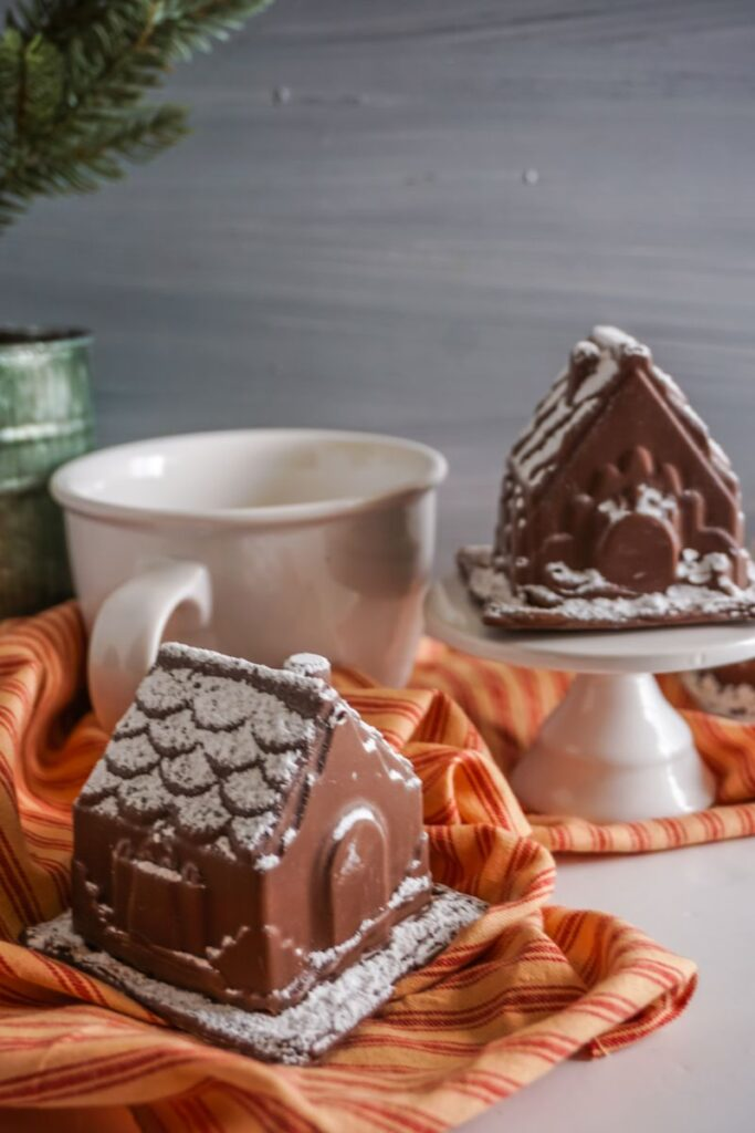 Gingerbread House Hot Cocoa Bombs on stand with mug on an orange and red cloth