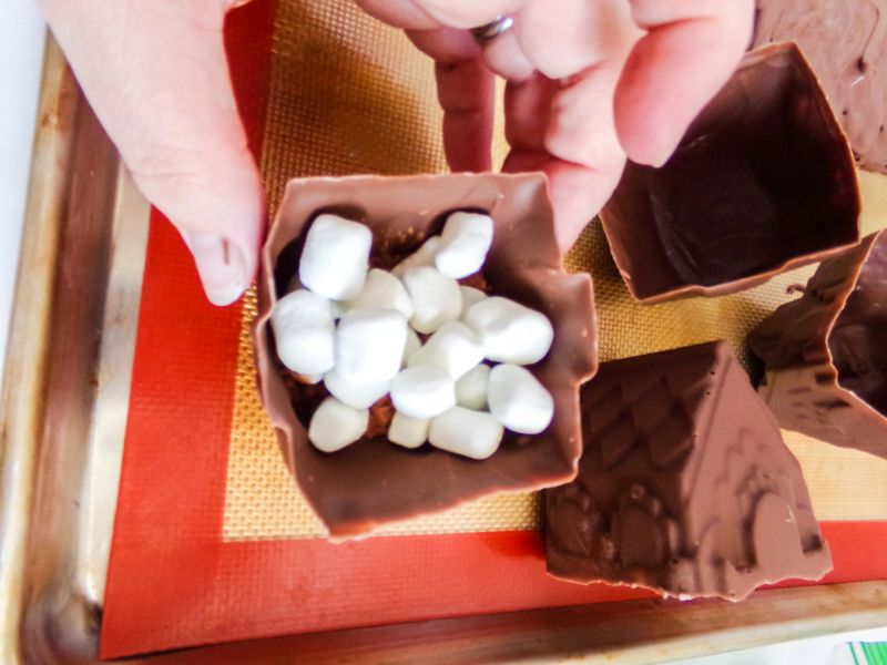 adding hot cocoa ingredients into the mold