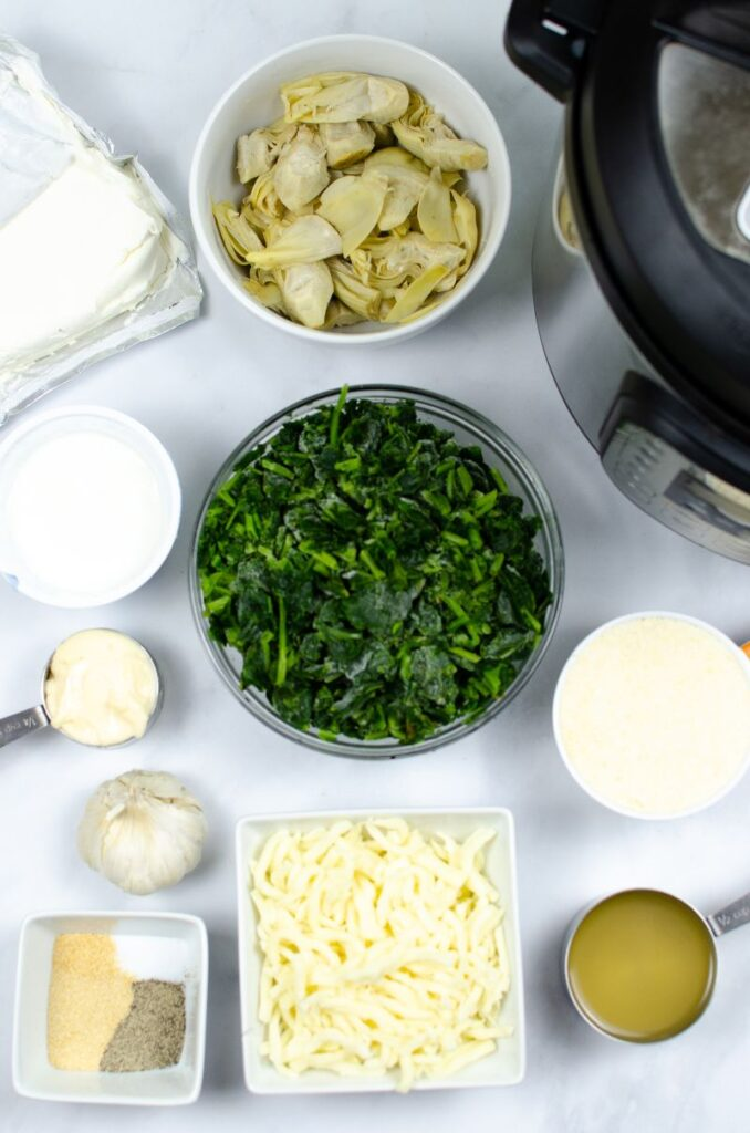 Ingredients for the spinach and artichoke heart dip in different bowls next to an instant pot.