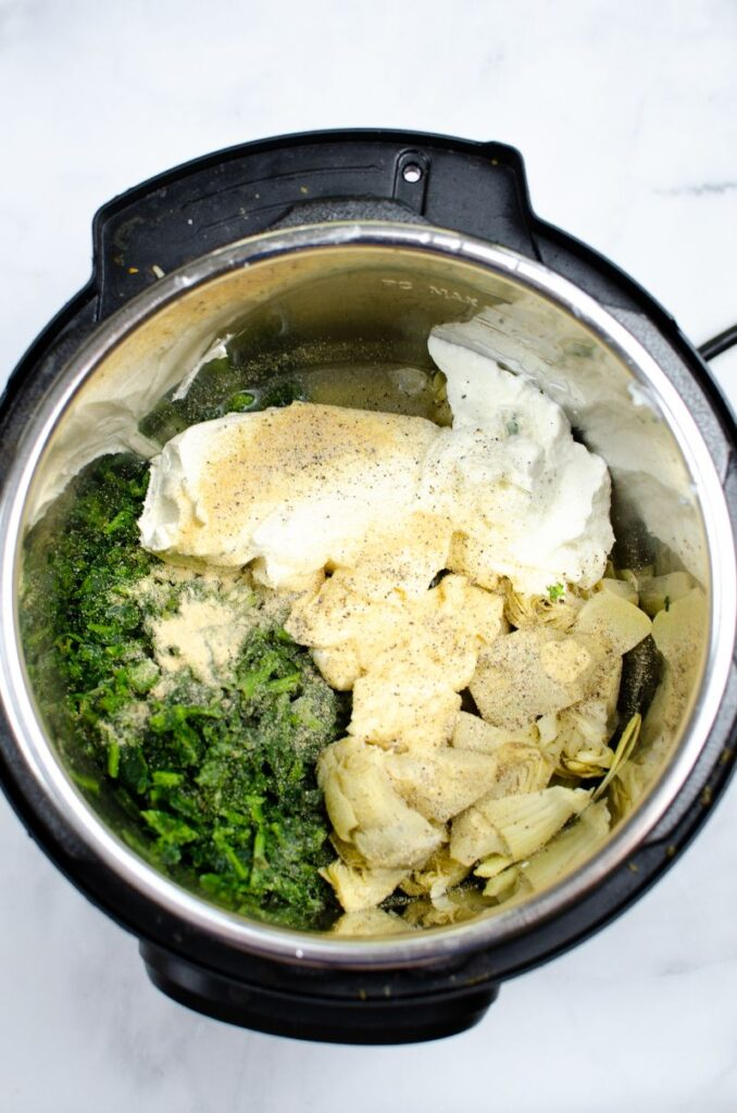 Artichoke hearts, spinach, cream cheese and spices in an instant pot.