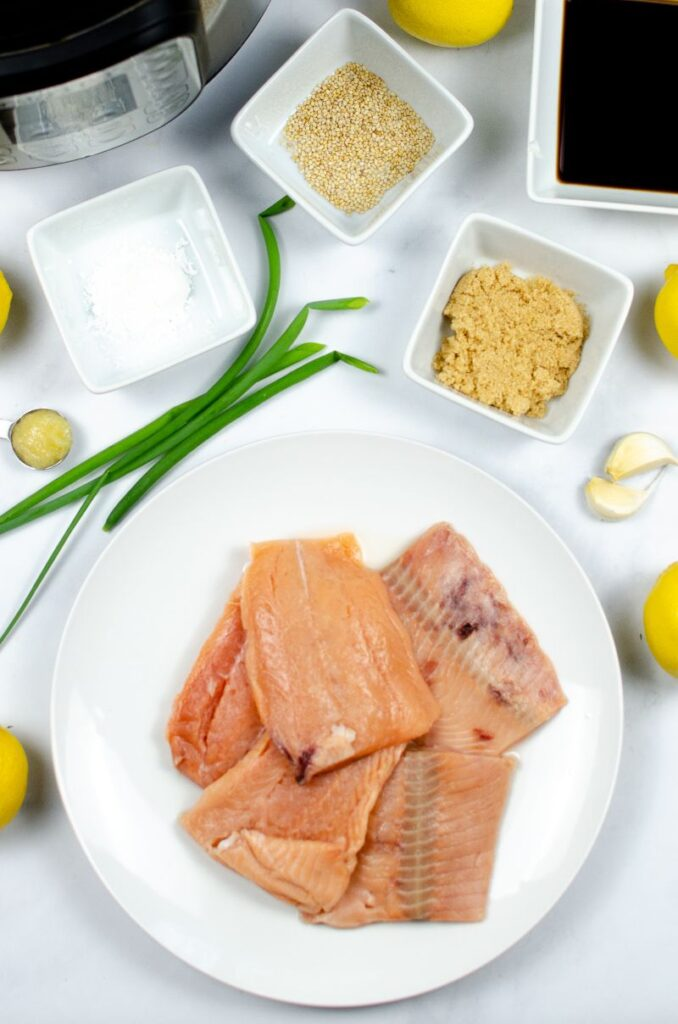 Salmon and other ingredients in white bowls next to an instant pot.