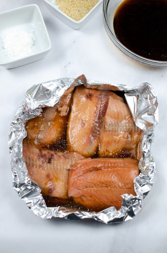 Salmon coated with sauce in aluminum foil next to ingredients in white and glass bowls