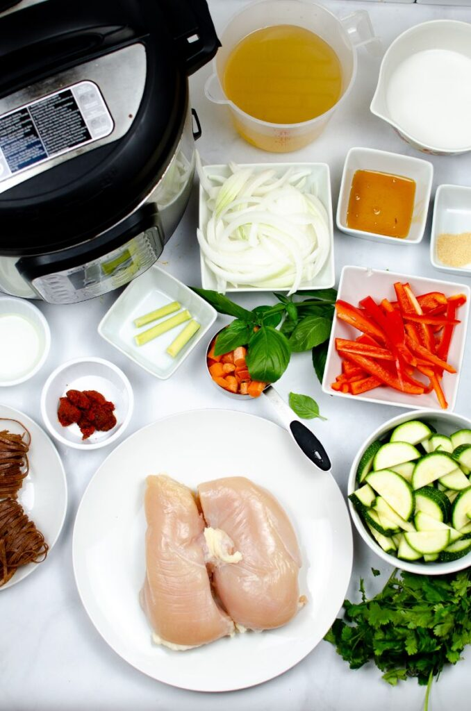 an instant pot and the ingredients needed to make Instant Pot Thai Red Chicken Curry